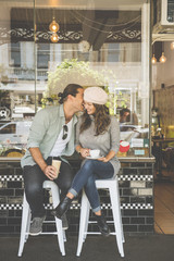 Laughing couple sitting on stools outside coffee shop