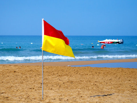 red and yellow flag on beach marking safe swimming area