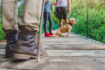 Family with dog on wooden suspension bridge