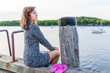 Young happy smiling woman sitting on edge of dock in Bar Harbor, Maine looking at water and bay