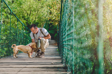 Hiker with dog resting on wooden suspension bridge