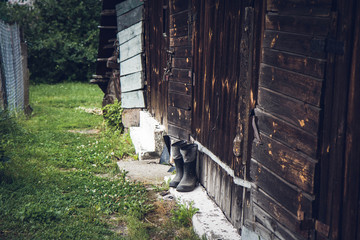 Wooden barn with rubber-soled felt boots standing in front of it