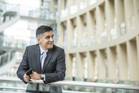 Mixed Race businessman leaning on railing in lobby holding cell phone