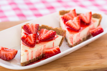 Two Delicious Pieces of Cheesecake With Strawberries For Dessert