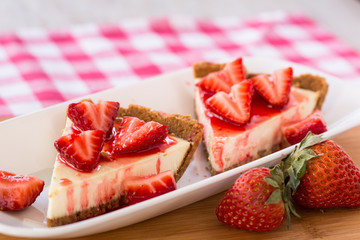 Two Tasty Slices of Cheesecake with Cut Up Strawberries