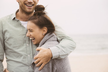 Laughing Caucasian couple hugging on beach