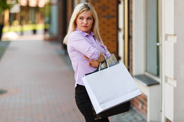 Frustrated woman with shopping bags near store