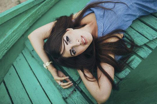 Caucasian woman laying on green boardwalk