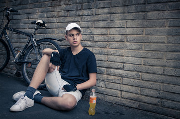 teenage boy with bike in front of a brick wall