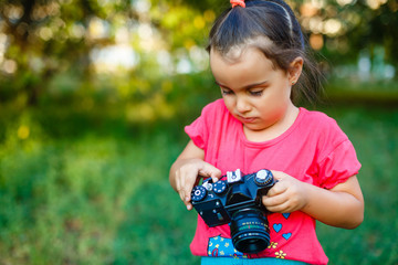 Portrait of young beautiful child with retro camera. Little girl with old photography camera in hands outdoors.