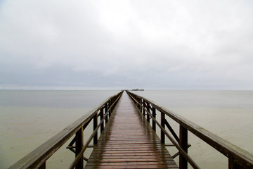 Endless jetty to the horizon. View to a turquoise sea and blue sky with white clouds
