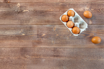 Raw eggs on wooden table, top view, free space