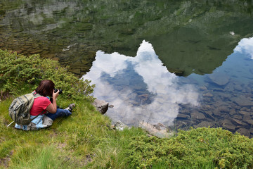 Mature woman takes pictures of a mountain lake with her digital camera, mountain peak reflection seen in the limpid water