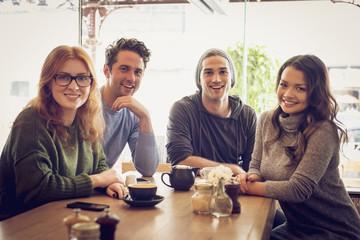 Portrait of friends smiling in coffee shop
