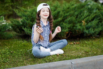 A happy cute little girl sitting on the grass in the park and listening to music via headphones and enjoying it.