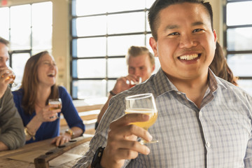 Portrait of smiling man drinking beer with friends in brew pub