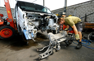 Mechanic removes the front axle of a van at Autoverwertung Truninger AG car recycling company in Rickenbach