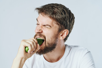 Man with a beard on a light background bites off a cucumber, portrait