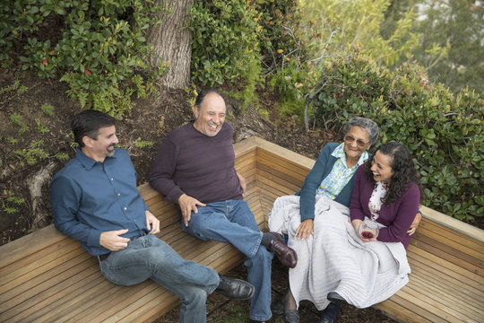 People sitting on bench and laughing