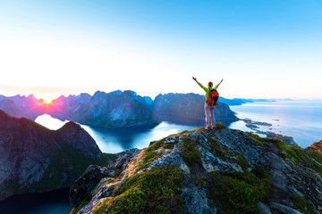 Hiker enjoying midnight sun during arctic summer, Reine, Lofoten, Norway