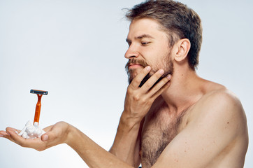 A man with a beard on a light background holds a razor and shaving foam