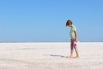 Cute little girl walking. Little girl relaxing on the Salt Lake. Young Girl enjoying the view of the salt lake.