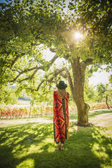 Hispanic woman wrapped in blanket standing under tree