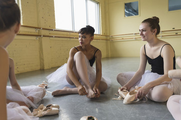 Women sitting on floor and talking in ballet studio