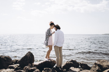 Middle Eastern couple standing on rocks near ocean