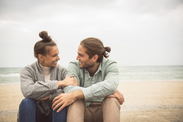 Caucasian couple sitting together on beach