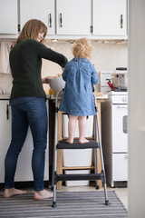 Girl standing on ladder cooking with mother in kitchen