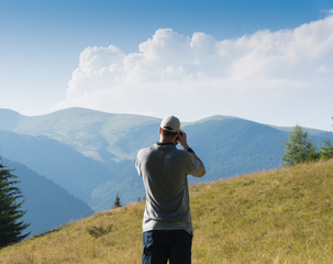 A man with a camera in the background of a mountain landscape