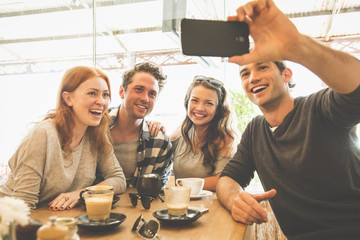 Friends posing for cell phone selfie in coffee shop