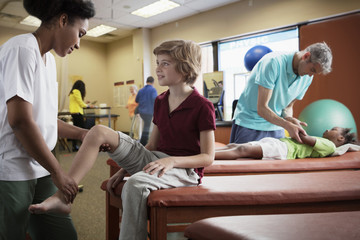 Physical therapist bending leg of boy