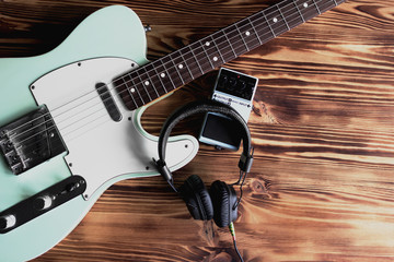 Electric guitar, pedal and headphones on the wooden table. Making music and sound recording concept.
