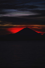 Bright tropical sunset and silhouettes of Agung volcano on the island of Bali in Indonesia.