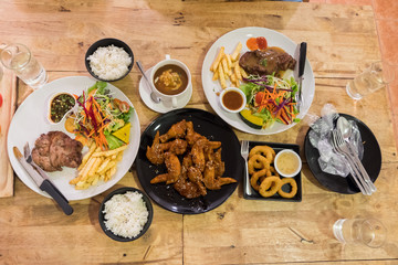 Top view of pork pepper steak with vegetable and french fries and sauce and chicken wingin and fried onions white plate on wooden table. Food set and knife and spoon with glove.