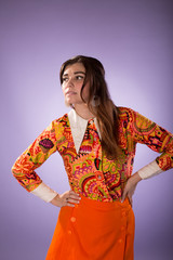 Young caucasian woman in vintage 1960's party fashion against purple background
