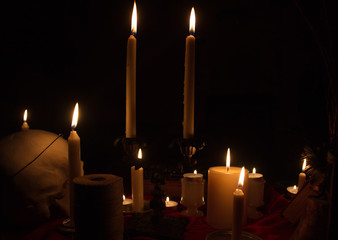 Burning candles and human skull in dark room. Halloween witchraft concept.