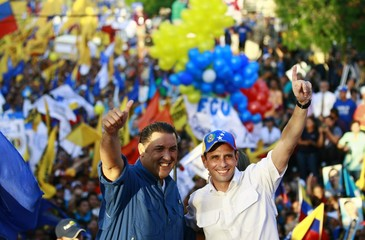 Opposition candidate Henrique Capriles raises his hands with Zulia's state governor Pablo Perez during a campaign rally in Maracaibo