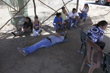 People rest while they wait to try to cross into Colombia close to the border at Paraguachon in the state of Zulia