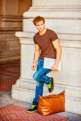 Young Man carrying laptop computer, bag, relaxing on street in New York