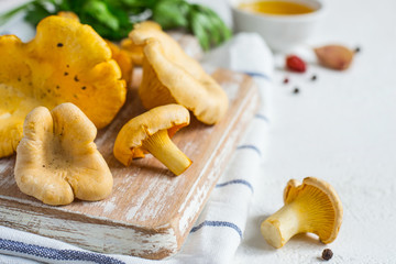 Raw chanterelle mushrooms on a cutting board closeup on white background