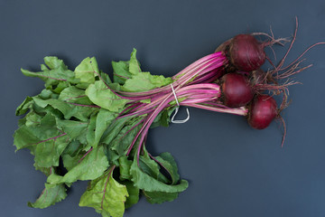 Five freshly picked beets with the greens photographed on a charcoal gray background.