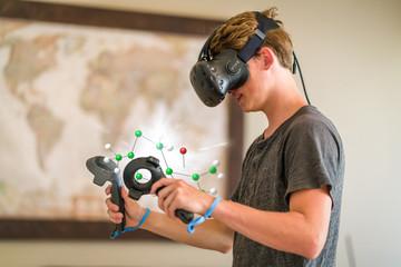 A teenage student wearing a virtual reality headset to study.