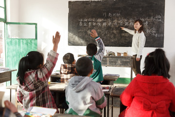 Teacher pointing at blackboard with Chinese script in classroom