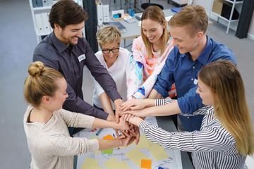 motiviertes junges team im büro hält die hände zusammen