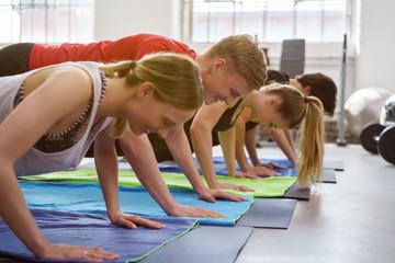 gruppe im fitness-studio macht liegestütz