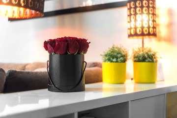 Roses in black box standing on the white table