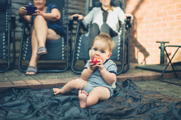 Little baby eating a peach outside